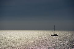 Shiny sea and sailboat Stock Image