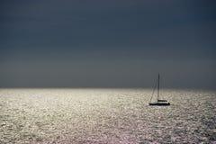 Shiny sea and sailboat. Shiny sunset sea and silhouette of sailboat Stock Image