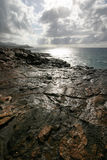 Shiny Shore. Rocky shore of Hawaii reflecting the sunny, cloudy sky Royalty Free Stock Photo