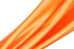 Shiny silk orange drapery. Isolated on a white background Stock Image