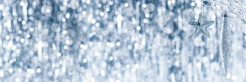 Shiny silver christmas ornaments hanging on a tree, with defocused christmas lights. royalty free stock images