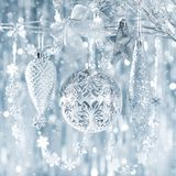 Shiny silver christmas ornaments hanging on a tree, with defocused christmas lights. royalty free stock image