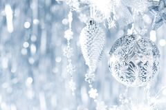 Shiny silver christmas ornaments hanging on a tree, with defocused christmas lights in the background. Christmas background. royalty free stock photo