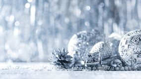 Shiny silver christmas present and beautiful ornaments, with defocused christmas lights in the background. Christmas banner royalty free stock image