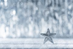 Shiny silver christmas star with defocused christmas lights in the background. Christmas background. Shiny silver christmas star with defocused christmas lights royalty free stock image