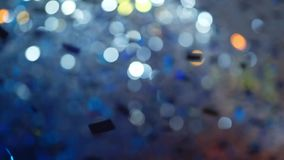 Shiny silver confetti fall at the party. Indoors stock footage