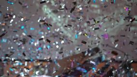 Shiny silver confetti fall at the party. Indoors stock video footage