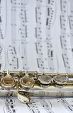 A silver flute on sheet music royalty free stock image
