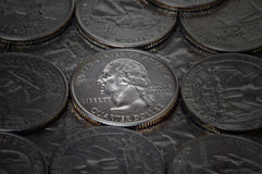 Shiny Silver Quarter. A glowing silver quarter in a batch of others Royalty Free Stock Images