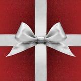 Shiny silver satin ribbon bow on red Royalty Free Stock Photo