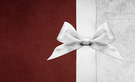 Shiny silver satin ribbon bow on red background Royalty Free Stock Image