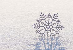 Shiny silver snowflake on brilliant snow, winter Christmas conce Stock Image