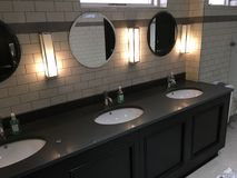Shiny sinks. 3 sinks in a tiled restroom with mirrors above and Stock Images