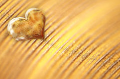 Shiny small golden heart on gold powder Stock Image