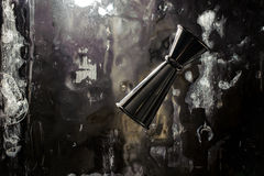 Shiny stainless steel jigger for alcoholic beverage on solid ice royalty free stock image