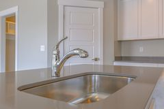 Shiny stainless steel sink and faucet on the countertop inside a kitchen royalty free stock images
