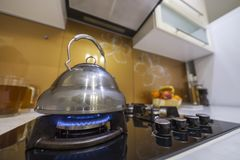 Shiny stainless tea kettle teapot with boiling water on burning gas stove on modern kitchen yellow interior background.  stock photos