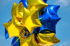 Shiny Star Balloons. Bunch of Blue and Yellow Mylar Balloons with Sky Background Royalty Free Stock Image