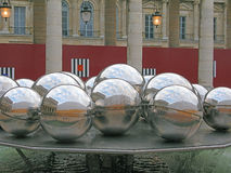 Shiny steel balls. PARIS, FRANCE - JANUARY 2, 2010: Royal castle courtyard with shiny steel ball sculpture and people watching on January 2, 2010 in Paris Stock Photography
