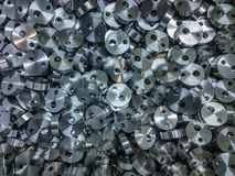 Shiny steel cylindrical parts background. Pile of many turning drilled engineering parts Stock Photos