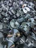 Shiny steel cylindrical parts background. Pile of many turning drilled parts with selective focus Royalty Free Stock Image