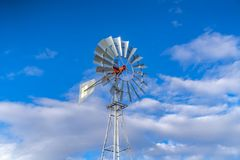 Shiny steel windpump against a vibrant blue sky with cottony clouds. This multi-bladed windpump is a type of windmill used for pumping water royalty free stock photo