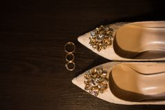 Shiny stones on the beige shoes. Women`s beige shoes on heels decorated with precious brilliant stones, nobody. Wedding shoes with sparkling stones. Heels Stock Photography