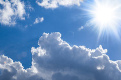 Shiny sun - bright clouds. Blue sky with sun and bright puffy clouds Royalty Free Stock Image
