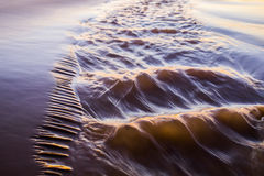 Shiny tropic sea wave on golden beach sand in sunset light Royalty Free Stock Photo