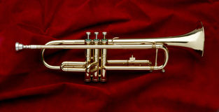 Shiny trumpet on red suede. Full shot of shiny trumpet on red suede background Stock Photo