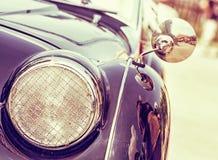 Shiny vintage car, retro photo filter. Shiny vintage car. Retro photo filter. Detail view of the headlight. Retro car. Front light. Retro automobile scene Stock Photo