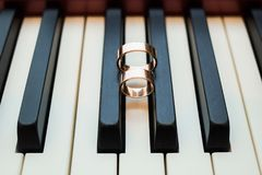 Shiny wedding golden rings on black and white keys of piano Royalty Free Stock Image