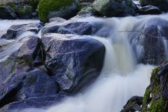 Shiny wet rocks in rapidly flowing small river royalty free stock photos