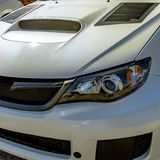 Shiny white car with a hood scoop and vents royalty free stock images