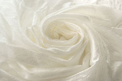 Shiny white cloth folded in the shape of a spiral. Wrinkled white cloth close up Royalty Free Stock Image