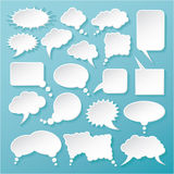 Shiny white paper bubbles for speech on an blue background. Stock Photo