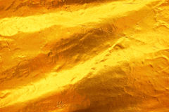 Shiny yellow leaf dark gold foil texture background royalty free stock images