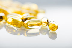 Shiny yellow vitamin e fish oil capsule Stock Photo