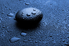 Shiny zen stone with water drops. Blue shiny zen stone with water drops Stock Image
