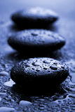 Shiny zen stones with water drops. Toned blue Stock Photos