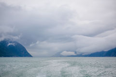 A ship afar off. A ship is afar off in the vast space of water, mountains and ominous clouds Royalty Free Stock Photography