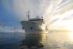 Ship in the antarctic. White ship cruising through the antarctic at sunset Stock Images