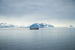 Ship in arctic ocean with snowy mountains behind Royalty Free Stock Photos