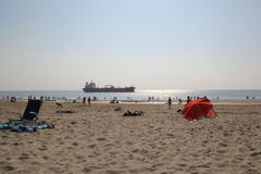 SHIP AND BEACH. A large cargo ship slowly sails down the beach Stock Photo