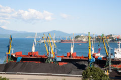 Ship is being loaded with coal in port of Nakhodka Stock Photo