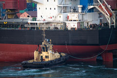 Ship berthing at port with tug assistance Royalty Free Stock Image