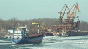 Ship blocked in frozen port, cranes working. UHD 4K stock video