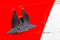 Ship Bow Anchor Red. Ship boat bow with anchor black with red paint hull closeup in hatbor port stock photo