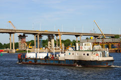 Ship, bridge and construction. Old ship in Rostov on Don delievers cargo for the construction of new bridge over the Don river Royalty Free Stock Photos