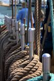 Ship brown ropes on the rails with a man on the background. stock photography